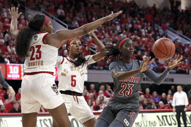 Louisville guard Jazmine Jones (23) passes while North Carolina State guard Grace Hunter (23) and forward Jada Boyd (5) defend during the first half of an NCAA college basketball game in Raleigh, N.C., Thursday, Feb. 13, 2020. (AP Photo/Gerry Broome)