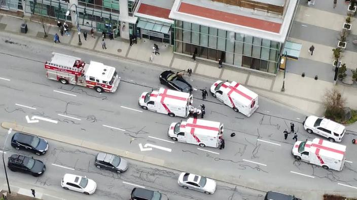 Ambulances and emergency personnel are seen on a road at Lynn Valley Plaza after a stabbing at a public library in a suburb in Vancouver