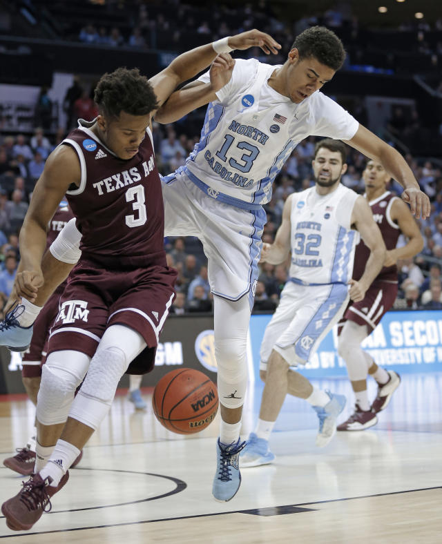 North Carolina's Cameron Johnson (13) and Texas A&M's Admon Gilder (3) battle for the ball during the first half of a second-round game in the NCAA men's college basketball tournament in Charlotte, N.C., Sunday, March 18, 2018. (AP Photo/Bob Leverone)