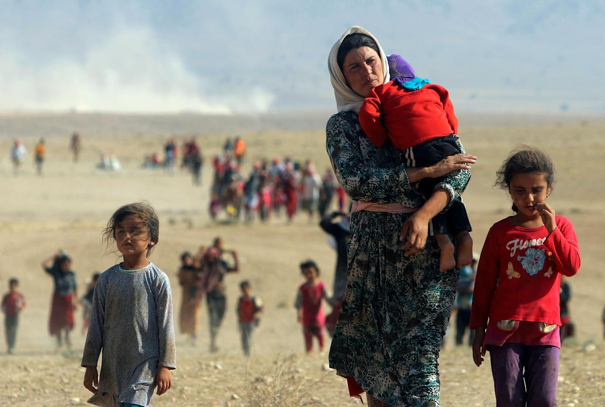 Displaced people from the minority Yazidi sect, fleeing violence from forces loyal to the Islamic State in Sinjar town, walk towards the Syrian border on the outskirts of Sinjar mountain near the Syrian border town of Elierbeh of Al-Hasakah Governorate in this August 11, 2014.