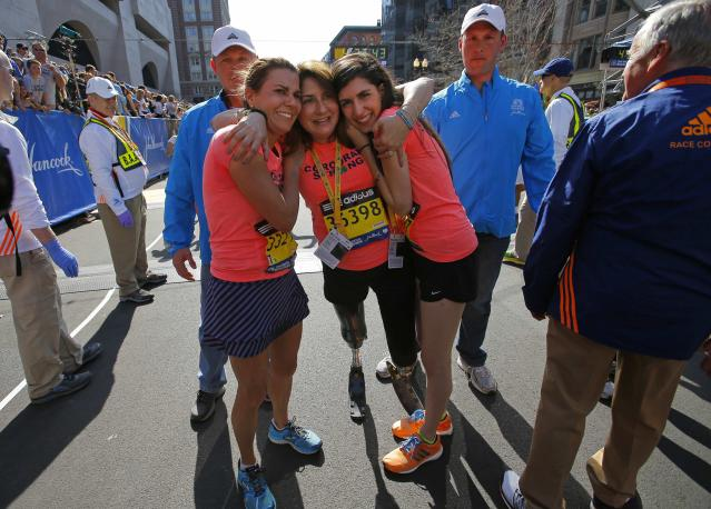 2013 Boston Marathon survivors Celeste Corcoran (C) and her daughter Sydney (R) hug together with Celeste's sister Carmen Acabbo (L), who ran the 118th Boston Marathon, after crossing the finish line in Boston, Massachusetts April 21, 2014. REUTERS/Brian Snyder (UNITED STATES - Tags: SPORT ATHLETICS)