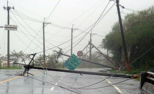 Utility poles lie on the road after being blown down during typhoon Tembin in Taitung, eastern Taiwan