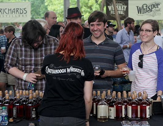 Sara Keith of the Chattanooga Whiskey Company pours samples for, from left to right, Daniel Sutherland, Wes Okes and Laura Devilbliss at the Tennessee Whiskey Festival in Chattanooga, Tenn., Sept. 21, 2013