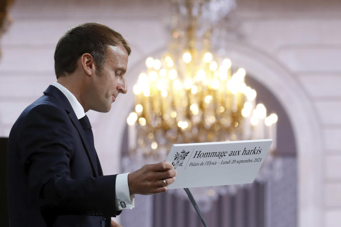 French President Emmanuel Macron holds a sign as he delivers a speech during a meeting in memory of the Algerians who fought alongside French colonial forces in Algeria's war, known as Harkis, at the Elysee Palace in Paris, Monday, Sept. 20, 2021. Macron's speech is the latest step in his efforts to reconcile France with its dark colonial past, especially in Algeria. (Gonzalo Fuentes/Pool Photo via AP)