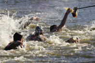 Swimmers grab a bottle at a feeding station during the men's marathon swimming event at the 2020 Summer Olympics, Thursday, Aug. 5, 2021, in Tokyo, Japan. (AP Photo/Jae C. Hong)