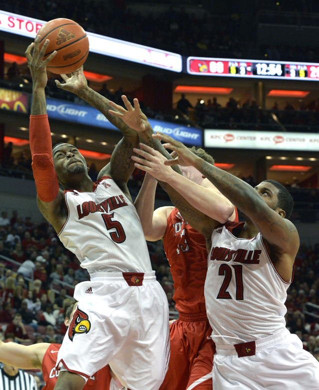 Louisville's Kevin Ware, left, pulls down a rebound away from the reach of Cornell's Dwight Tarwater, center, and Louisville's Chane Behanan during the second half of an NCAA college basketball game on Friday, Nov. 15, 2013, in Louisville, Ky. Louisville defeated Cornell 99-54. (AP Photo/Timothy D. Easley)