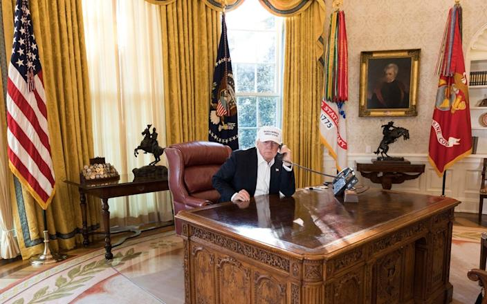 The White House has released photographs showing President Donald Trump apparently working hard over the weekend in a bid to avert the impending government shutdown. The president spent his inauguration anniversary at his desk rather than partying with supporters at a planned Mar a Lago celebration as he struggled to make headway on resolving the crisis. A second senate vote on the spending bill has been scheduled for 1am (6am GMT) Monday as the government shutdown enters the working week. But as the deadline loomed, it seemed the two sides were at an impasse over the question of the Deferred Action for Childhood Arrivals policy. Democrats insist a provision to protect the dreamers, those who were brought to the country illegally as children by their parents, is included. The Republicans say they will negotiate that once the government is up and running again. On Sunday morning, the president tweeted: Great to see how hard Republicans are fighting for our Military and Safety at the Border. The Dems just want illegal immigrants to pour into our nation unchecked. If stalemate continues, Republicans should go to 51% (Nuclear Option) and vote on real, long term budget, no C.R.'s!— Donald J. Trump (@realDonaldTrump) January 21, 2018 Mr Trump walks along the West Wing Colonnade Credit: Official White House Photo The photographs, released on Saturday, show the president walking along the West Wing Colonnade from his residence to the Oval Office where he remained behind close doors for much of the day. Another captured a steely-faced Mr Trump holding a phone to his ear receiving updates from Capitol Hill while wearing a Make America Great Again baseball hat. And a third picture had him surrounded by smiling senior staff including his daughter Ivanka, son in law Jared Kushner, communications director Hope Hicks and press secretary Sarah Huckabee Sanders. President Donald J. Trump meets with White House senior staff members including Sarah Huckabee Sanders and Hope Hicks Cred