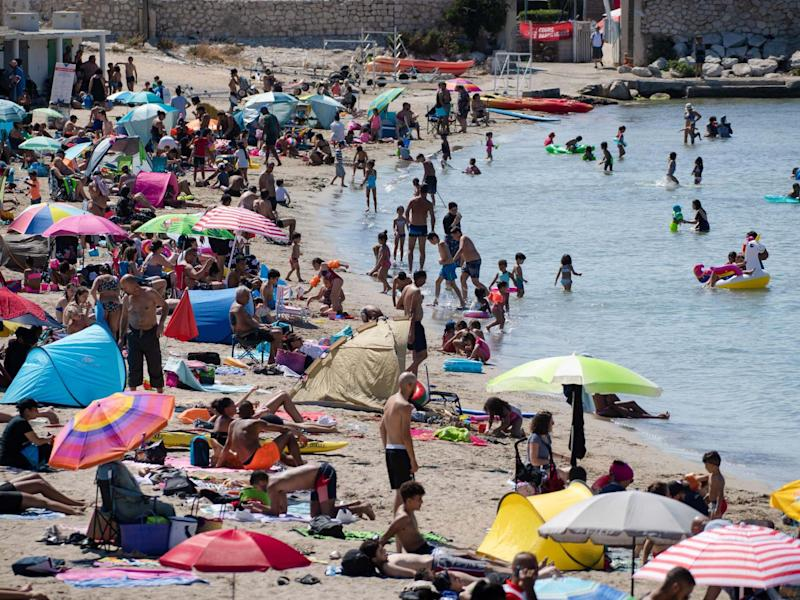 """People enjoy the sea at the """"Pointe Rouge"""" beach at the beginning of a heatwave in Marseille, southern France, 27 July 2020: Clement Mahoudeau/AFP via Getty Images"""