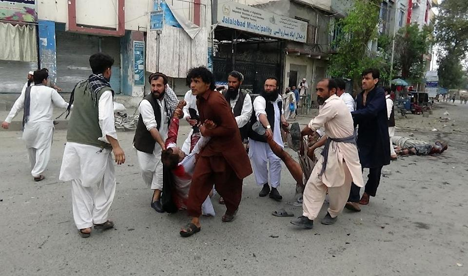 Residents assist wounded men after a suicide attack outside a bank in the city of Jalalabad, eastern Afghanistan, on April 18, 2015 (AFP Photo/)