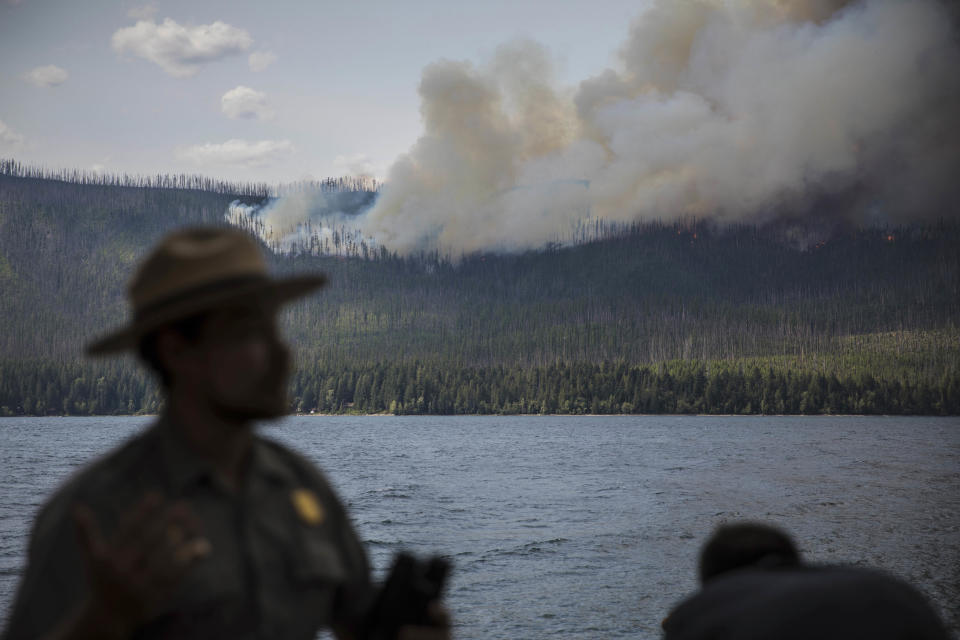 FILE - In this Sunday, Aug. 12, 2018 file photo provided by the National Park Service, an interpretive ranger talks to visitors about the Howe Ridge Fire from outside Lake McDonald Lodge in Glacier National Park, Mont. Wildfires burning in the U.S. this summer have upended plans for countless outdoor adventures. Campers, hikers, rafters and other outdoor enthusiasts have had to scrap or change plans or endure awful smoke. (National Park Service via AP,File)