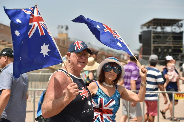 A couple wave flags to mark Australia Day in Sydney (AFP Photo/PETER PARKS)