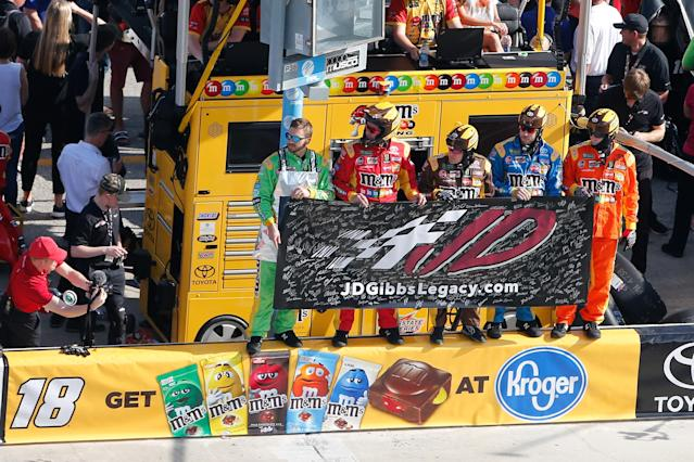 Kyle Busch's pit crew stands on the pit road wall, holding a banner to honor the late J.D. Gibbs. (Getty Images)