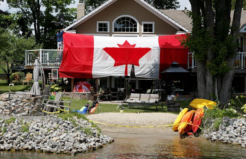 A man hangs a large Canadian flag on the deck of his cottage to celebrate Canada Day on Big Rideau Lake in Rideau Ferry, Ontario, Canda July 1, 2016. REUTERS/Gary Cameron