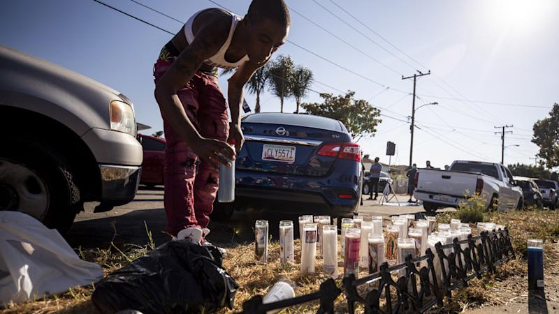 A person places a candle where Dijon Kizzee was shot