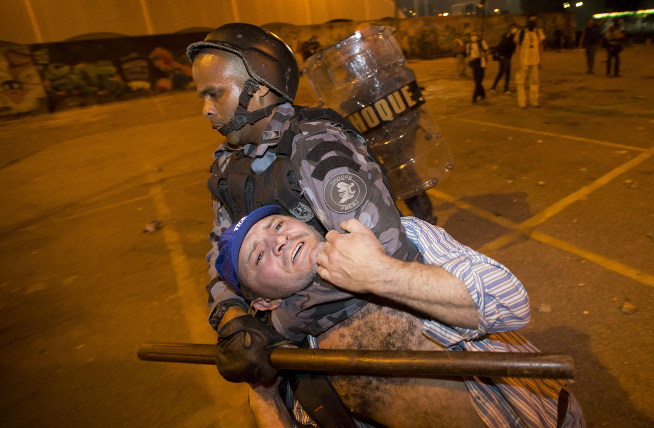 Military police detain a man during an anti-government protest in Rio de Janeiro, Brazil, Thursday, June 20, 2013. More than half a million Brazilians poured into the streets of at least 80 Brazilian cities Thursday in demonstrations that saw violent clashes and renewed calls for an end to government corruption and demands for better public services. Riot police battled protesters in at least five cities, with some of the most intense clashes happening in Rio de Janeiro, where an estimated 300,000 demonstrators swarmed into the seaside city's central area. (AP Photo/Victor R. Caivano)