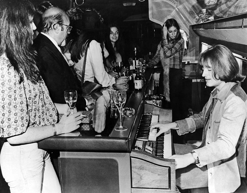 "<p>John Paul Jones of Led Zeppelin plays electric organ on board a private Boeing 720B airliner known as ""The Starship"" used by the band on tour in 1973. </p>"