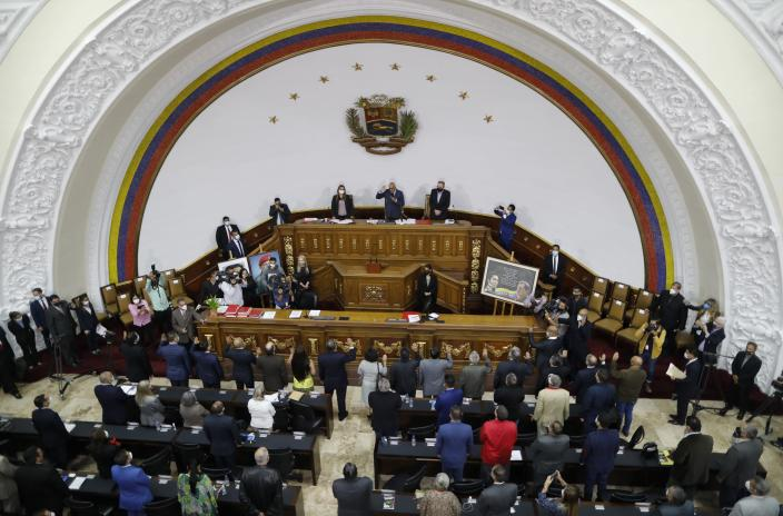 National Assembly President Jorge Rodriguez, top center, swears in Venezuela's new National Electoral Council directors, during an extraordinary session at the National Assembly in Caracas, Venezuela, Tuesday, May 4, 2021. The National Assembly, with an overwhelming pro-government majority, on Tuesday appointed two recognized opponents as members of the new board of the National Electoral Council of Venezuela. (AP Photo/Ariana Cubillos)