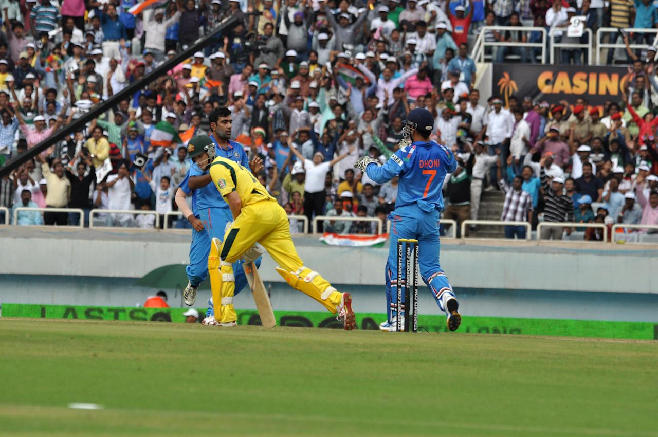 Dhoni and Ashwin celebrate the wicket of Adam Voges during the 4th ODI between India and Australia at JSCA Stadium in Ranchi on Oct. 23, 2013. (Photo: IANS)