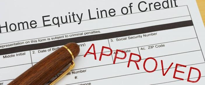 Applying for a Home Equity Line of Credit Approved, Home Equity Line of Credit application form with a pen on a desk with an approved stamp