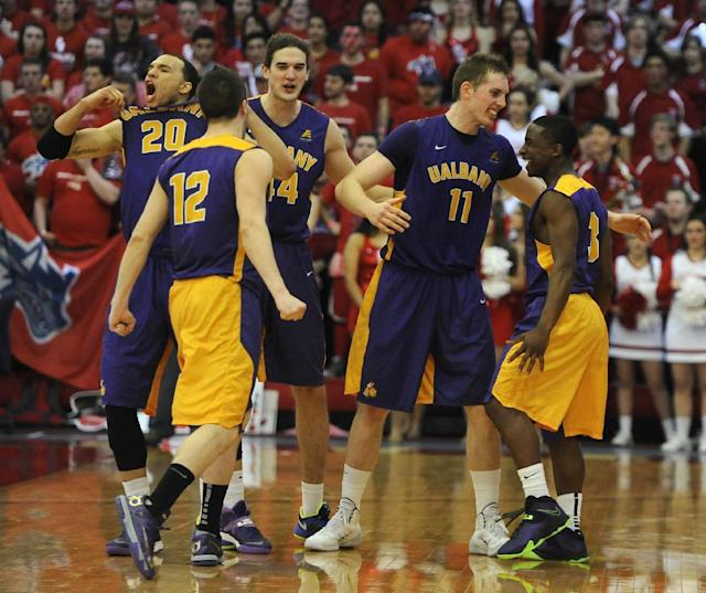 Albany' Gary Johnson (20), Peter Hooley (12), John Puk (44), Luke Devlin (11) and DJ Evans (3) celebrate after Albany beat Stony Brook 69-69 in an NCAA college basketball game to win the championship of the America East Conference tournament Saturday, March 15, 2014, in Stony Brook, N.Y. (AP Photo/Kathy Kmonicek)