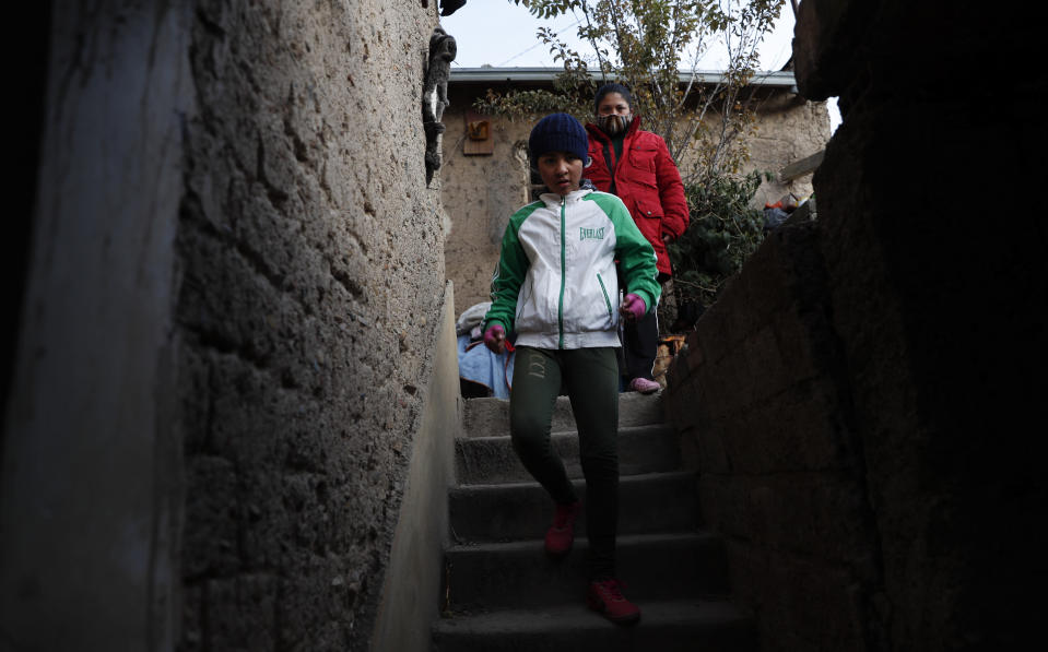 Gracce Kelly Flores, a 12-year-old boxer who goes by the nickname Hands of Stone, leaves home under the watch of her mother for a run as part of her daily boxing workout in Palca, Bolivia, early Thursday, June 10, 2021, amid the COVID-19 pandemic. At age 8, Flores defeated a 10-year-old boy, and with three national boxing medals under her belt, she dreams of reaching the women's boxing world championship. (AP Photo/Juan Karita)