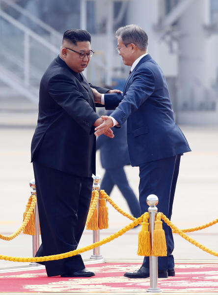 South Korean President Moon Jae-in, right, and North Korean leader Kim Jong Un gesture as they attend a welcoming ceremony at Sunan International Airport in Pyongyang in North Korea, Tuesday, Sept. 18, 2018. (Pyongyang Press Corps Pool via AP)