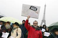Crowds observe a minute of silence in front of the Eiffel Tower in Paris