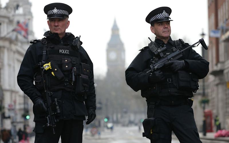 Armed police officers secure the area near the Houses of Parliament in central London - AFP