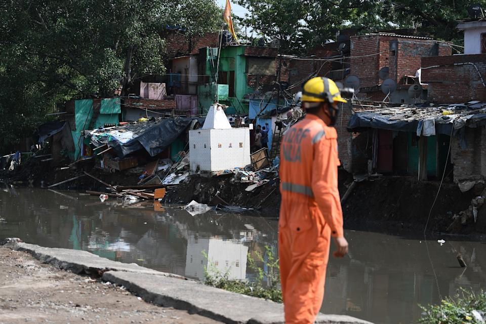 A National Disaster Response Force personnel inspects the area where some shanty houses collapsed into a canal due to heavy rains in New Delhi on July 19, 2020. (Photo by Sajjad HUSSAIN / AFP) (Photo by SAJJAD HUSSAIN/AFP via Getty Images)