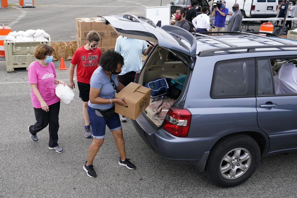 Volunteers with Catholic Charities of the Archdiocese of Washington distribute grocery boxes and ready-to-eat meals to recipients who have been affected by the coronavirus outbreak and economic downturn, Friday, Aug. 21, 2020, in a parking lot outside Robert F. Kennedy Memorial Stadium in Washington. (AP Photo/Patrick Semansky)