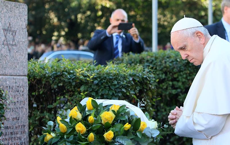 Pope Francis lays a bouquet of yellow roses at the foot of the Vilnius ghetto memorial and pays a silent tribute to Holocaust victims (AFP Photo/Petras Malukas)