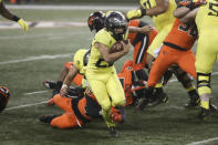 Oregon running back Travis Dye (26) slips a tackle by Oregon State outside linebacker Andrzej Hughes-Murray (49) during the second half of an NCAA college football game in Corvallis, Ore., Friday, Nov. 27, 2020. Oregon State won 41-38. (AP Photo/Amanda Loman)
