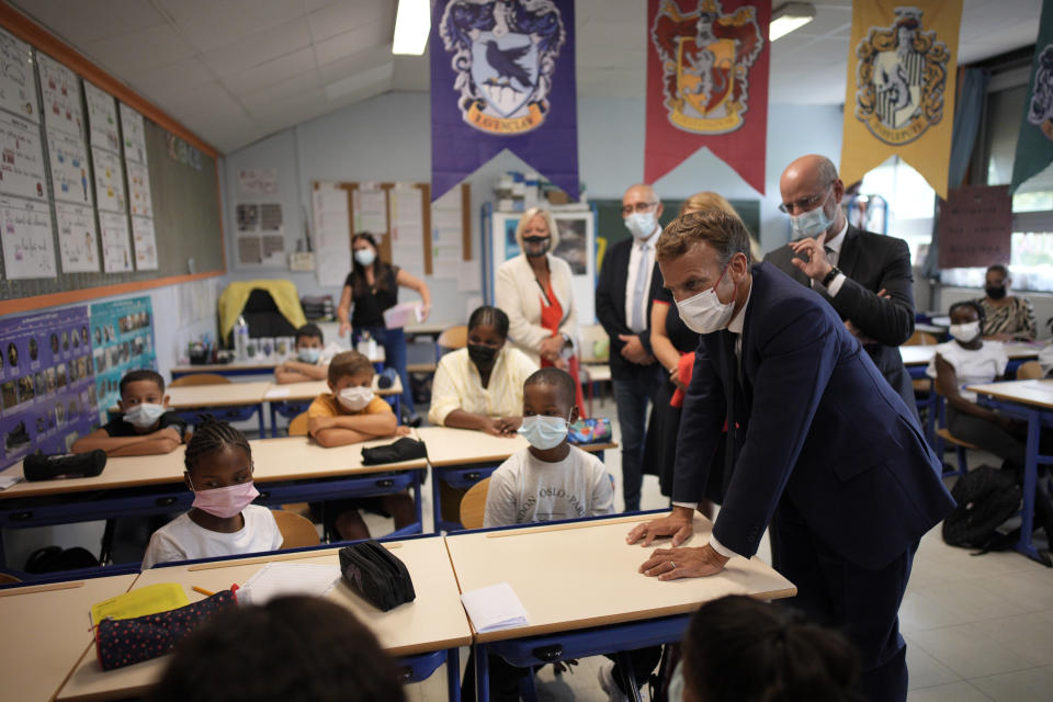 French President Emmanuel Macron, center, flanked with French Education, Youth and Sports Minister Jean-Michel Blanquer, right, speaks with children during a visit at Bouge primary school in Malpasse district of Marseille, southern France, Thursday Sept. 2, 2021 as twelve million children in France went back to school Thursday for the new academic year, wearing face masks as part of rules aimed at slowing down the spreading of the virus in the country. French President Emmanuel Macron, accompanied by several ministers, is on a three-day visit to the southern city of Marseille to address security, education and housing issues. (AP Photo/Daniel Cole, pool)