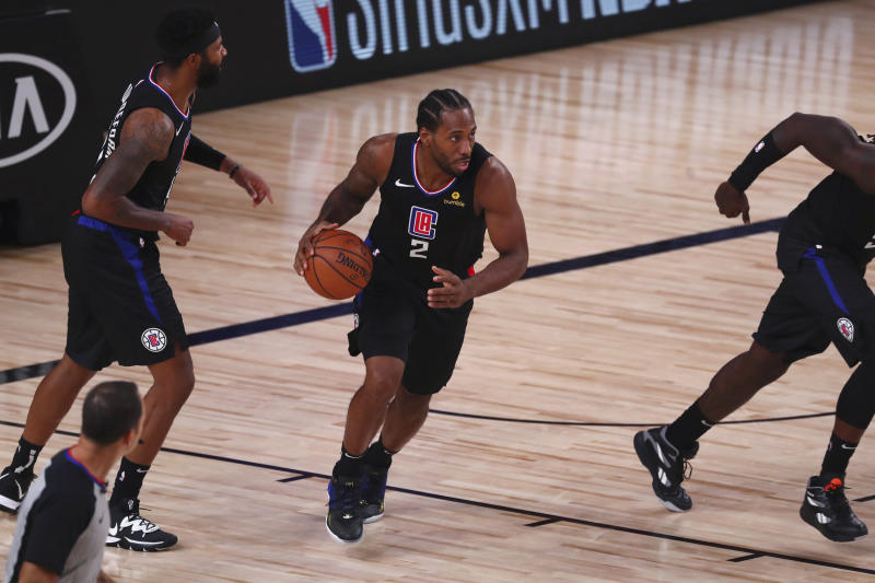 Kawhi Leonard with the ball, in between teammates, ready to take it up court.