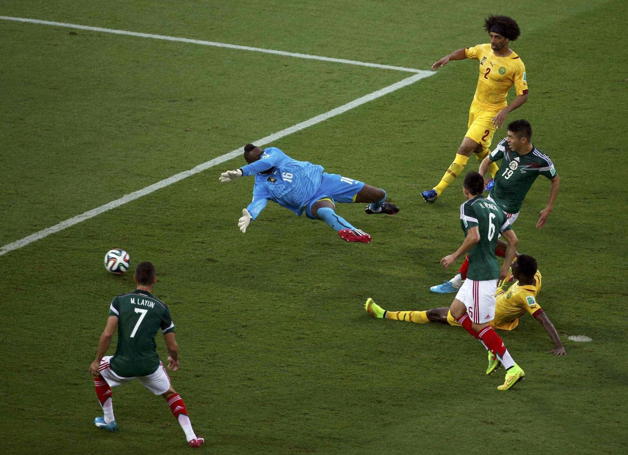 Mexico's Oribe Peralta (19) scores past Cameroon's goalkeeper Charles Itandje during their 2014 World Cup Group A soccer match at the Dunas arena in Natal June 13, 2014. REUTERS/Carlos Barria (BRAZIL - Tags: SPORT WORLD CUP TPX IMAGES OF THE DAY)  ATTENTION EDITORS: PICTURE 09 OF 15. TO FIND ALL IMAGES SEARCH 'TOPCUP REUTERS'