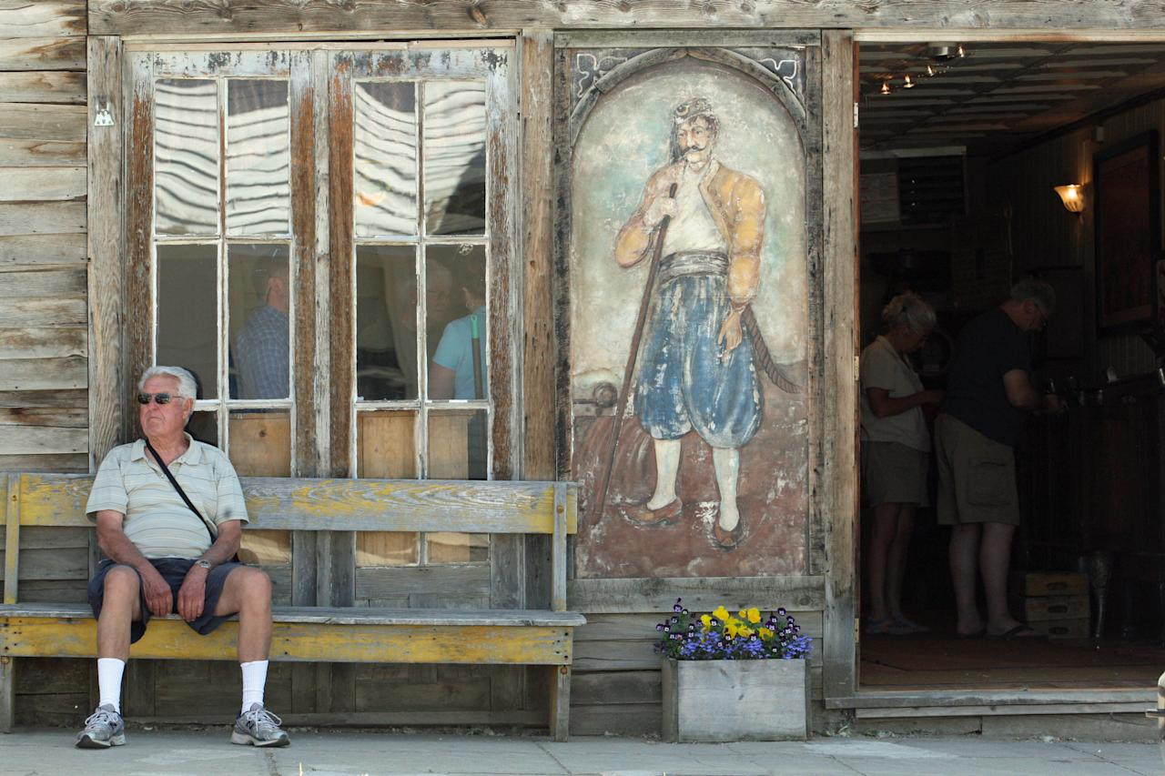 In this July 28, 2011 photo, a visitor sits outside the Gypsy Museum which houses an antique Gypsy fortune teller machine, in Virginia City, Mont., and has received multimillion dollar offers from curators including magician David Copperfield. Collectors say the 100-year-old machine that speaks your fortune may be the last of its kind. (AP Photo/Michael Albans)