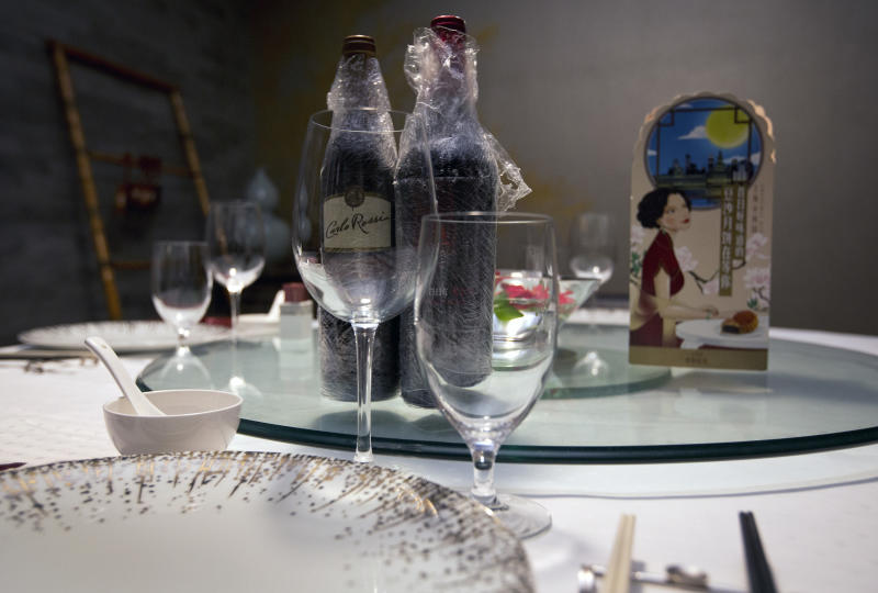 In this Thursday, Aug. 29, 2013 photo, bottles of western wine are placed on a dining table inside a private room of the Xiao Nan Guo restaurant in Beijing. China's high-end restaurants have gone into crisis under leader Xi Jinping's campaign to crack down on the kinds of party extravagances that have angered ordinary Chinese, such as dining on the public dime. To stem big losses and avoid the now-tarnished image of VIP banquet halls, these restaurants have been busy reinventing themselves. The Xiao Nan Guo restaurant in downtown Beijing specializes in elaborate Shanghai-style cuisine on white tablecloths with floral arrangements in private rooms behind thick, carved wooden doors. To attract more customers, it has revamped its menu to include new dishes worth under $15, said Zheng Yuming, the restaurant's general manager. (AP Photo/Andy Wong)