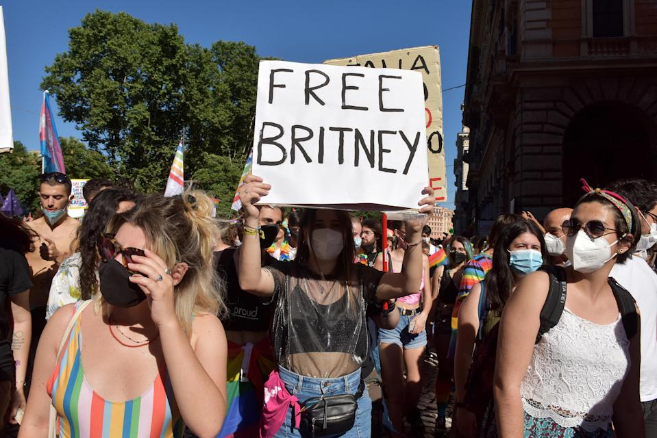 """Protesters wearing masks and holding up signs, including """"Free Britney"""""""