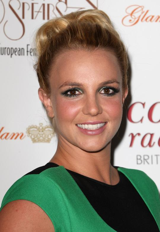 <p>A grown-up Spears sported a simple ponytail and green eye makeup at an appearance for her UK tour. (Photo: Getty Images)</p>
