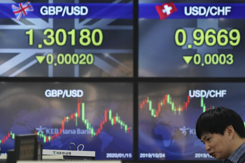 A currency trader talks near the screens showing the foreign exchange rates at the foreign exchange dealing room in Seoul, South Korea, Wednesday, Jan. 15, 2020. Asian shares have retreated as conflicting reports raised concerns over the likely outcome of a trade deal to be signed by the U.S. and China. (AP Photo/Lee Jin-man)