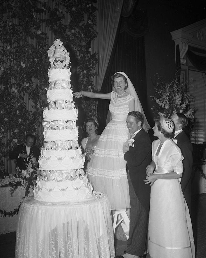 <p>Robert Sargent Shriver, Jr., steadies his bride, Eunice Kennedy, as she climbs onto a chair to cut the top of their wedding cake. The couple got in May 1953, a few months before her older brother, John F. Kennedy, tied the knot. </p>