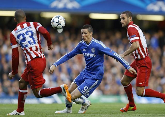 FILE - In this file photo dated Wednesday, April 30, 2014, Chelsea's Fernando Torres, centre tries to get past Atletico's Miranda, left during the Champions League semifinal second leg soccer match between Chelsea and Atletico Madrid at Stamford Bridge Stadium in London. According to an announcement released by Chelsea soccer club Friday Aug. 29, 2014, Italian club AC Milan have agreed terms for a two-year loan deal for striker Fernando Torres. (AP Photo/Kirsty Wigglesworth FILE)
