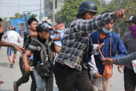 A man with a head injury is carried by others Monday, March 22, 2021 in Mandalay, Myanmar. The toll of protesters confirmed killed in Myanmar since last month's military takeover has reached 320, a group that verifies details of deaths and arrests announced Friday, March 26, 2021. (AP Photo)