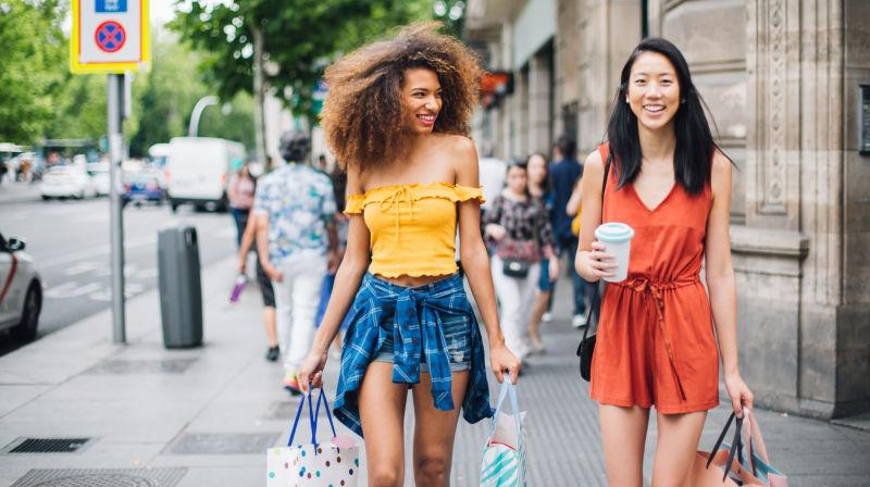 Two girls with shopping bags on a city street