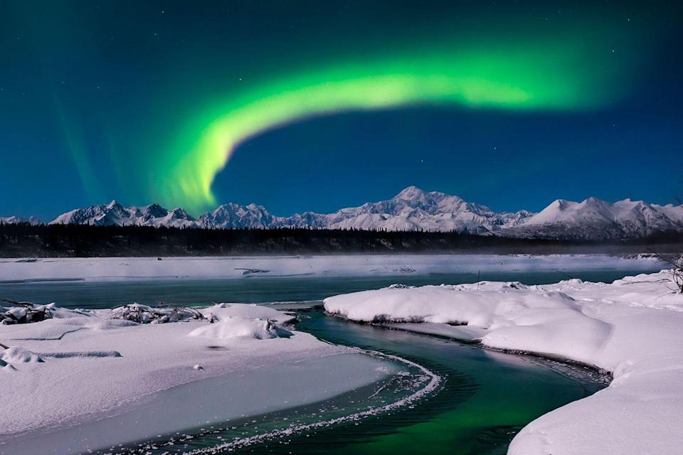<p>The Aurora Borealis glows over the snow-covered landscape in Denali State Park, Alaska.</p>