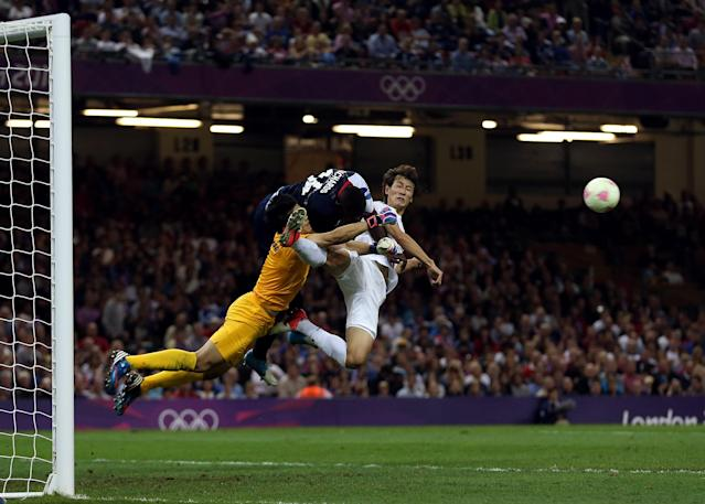 Micah Richards of Great Britain goes for the ball wiith Sungryong Jung of Korea and Dongwon Ji of Korea during the Men's Football Quarter Final match between Great Britain and Korea, on Day 8 of the London 2012 Olympic Games at Millennium Stadium on August 4, 2012 in Cardiff, Wales. (Photo by Julian Finney/Getty Images)