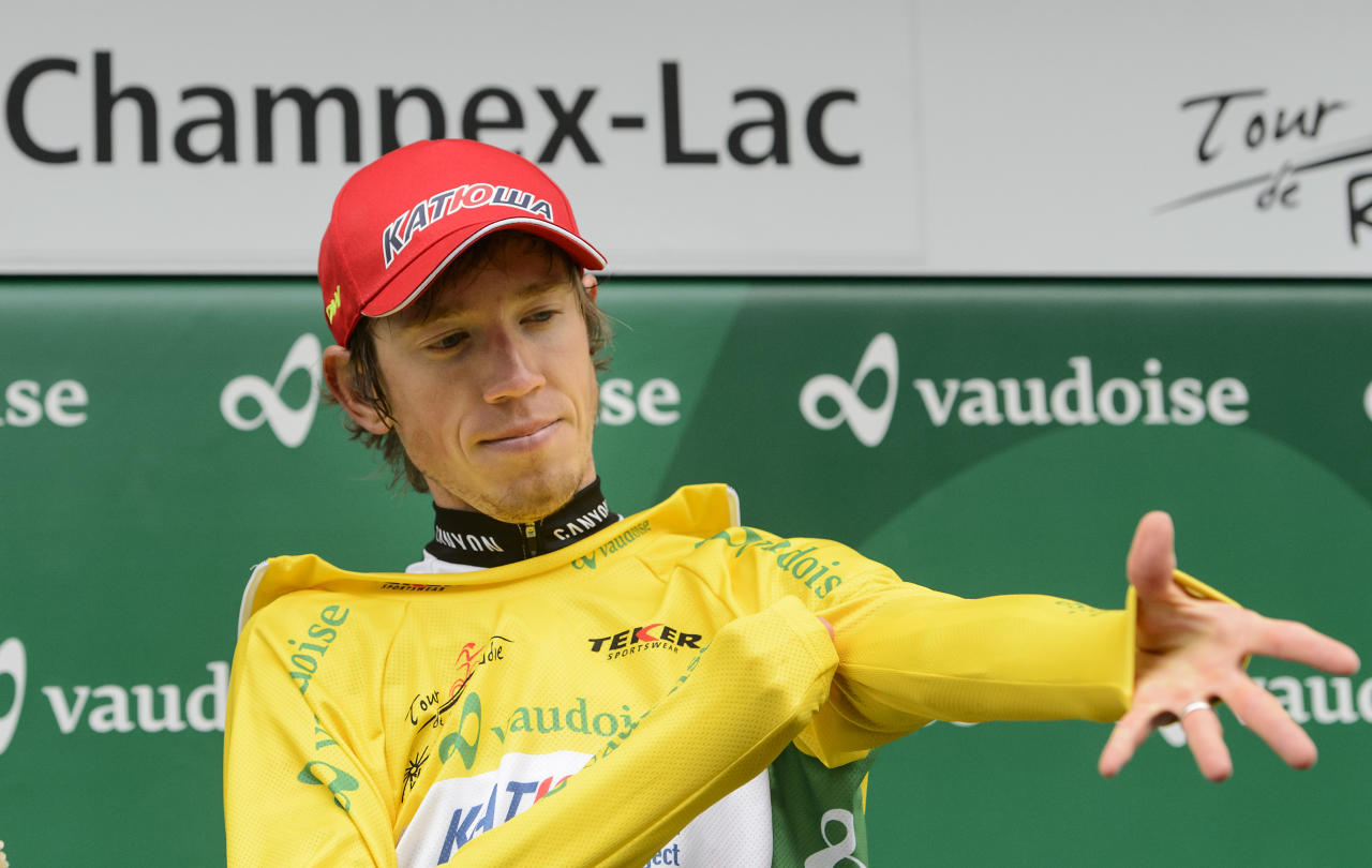 The new overall leader Russian Ilnur Zakarin of team Katusha dresses the yellow jersey on the podium after the fifth stage, a 162,7 km race between Fribourg and Champex-Lac, at the 69th Tour de Romandie UCI ProTour cycling race, in Champex-Lac, Switzerland, Saturday, May 2, 2015. (Jean-Christophe Bott/Keystone via AP)