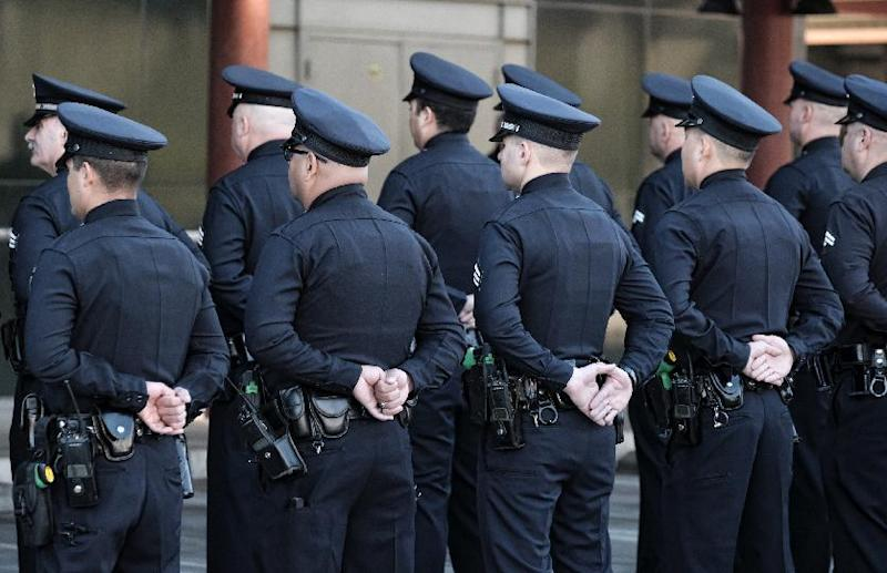 Los Angeles police officers stand at role call prior to a ceremony marking the 20th anniversary of an infamous gunbattle between police and two heavily armed bank robbers in Los Angeles on Tuesday, Feb. 28, 2017. The gathering Tuesday morning honored the officers involved in the February 1997 shootout that changed the way police departments nationwide arm officers. (AP Photo/Richard Vogel)