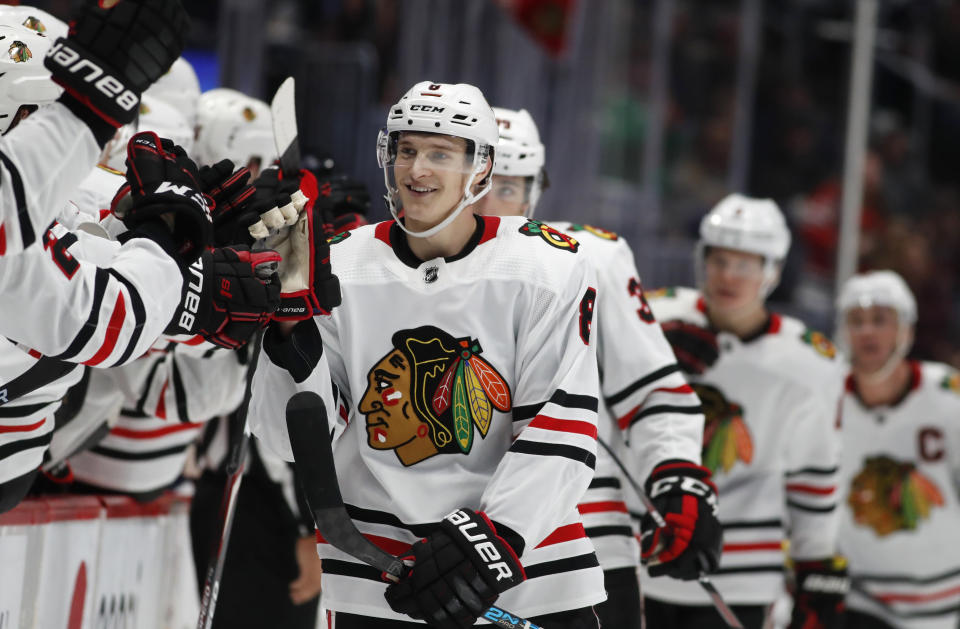FILE - Chicago Blackhawks left wing Dominik Kubalik, center, smiles as he is congratulated while passing the team box after scoring the go-ahead goal against the Colorado Avalanche during the third period of an NHL hockey game in Denver, in this Saturday, Dec. 21, 2019, file photto. Chicago won 5-3. The Chicago Blackhawks are going to remain the Blackhawks — and there is no sign of any change coming anytime soon. Speaking publicly for the first time Thursday, Dec. 17, 2020, since baseball's Cleveland Indians announced Monday they plan to change their name, Blackhawks CEO Danny Wirtz reiterated the same message the team shared this summer after lingering questions about Native American team names returned to the forefront.(AP Photo/David Zalubowski, File)