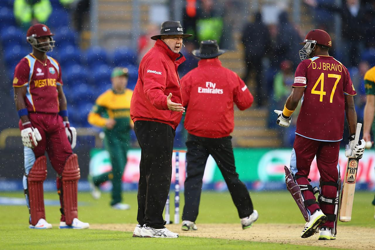 CARDIFF, WALES - JUNE 14:  Umpire Steve Davis (2L) stops play as rain arrives as Dwayne Bravo (R) and Darren Sammy (L) of West Indies have to accept that South Africa go through to the semi-final as the match is tied on the Duckworth/Lewis method during the ICC Champions Trophy Group B match between West Indies and South Africa at the SWALEC Stadium on June 14, 2013 in Cardiff, Wales.  (Photo by Michael Steele/Getty Images)